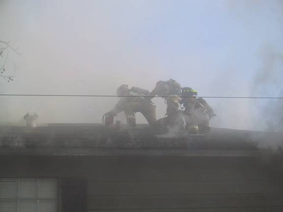 Fire fighters on the roof of the burning apartment