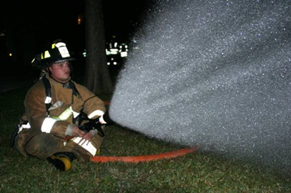 Fire fighter sitting on the ground spraying fire hose