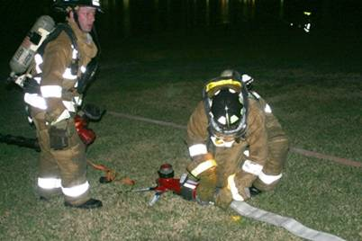 Fire fighters putting fire hose together