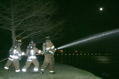 Fire fighters spraying a fire hose