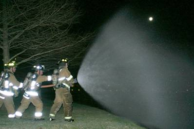 Fire fighters spraying fire hose