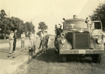 Men stand around an old fire truck