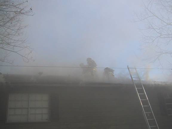 Fire fighters on roof of burning apartment