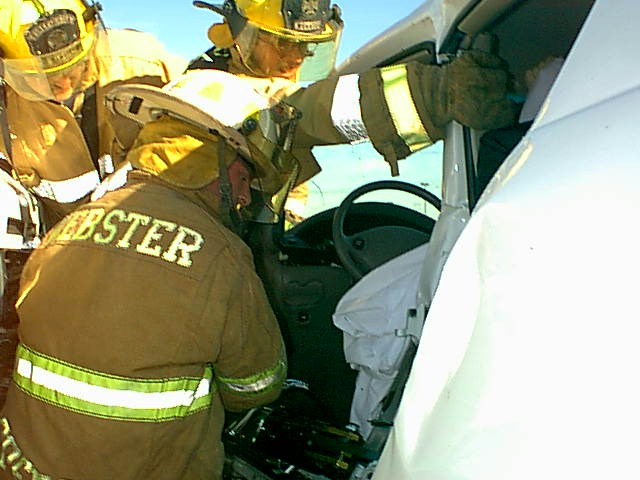 Fire fighters attempt to free a person from an automobile accident with the jaws of life