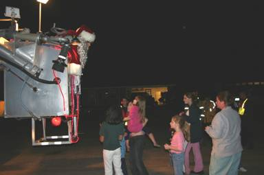 Santa in fire truck ladder