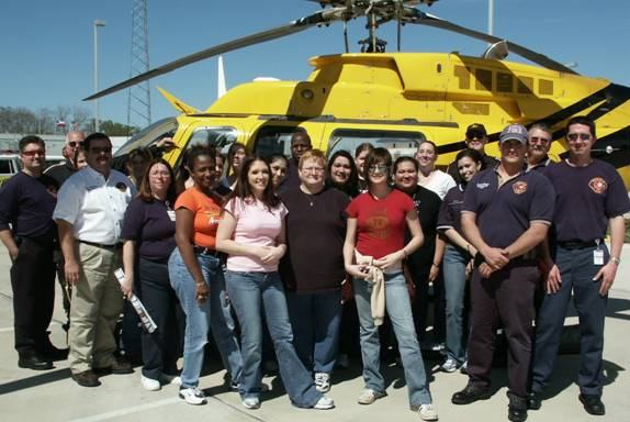 People posing in front of a helicopter